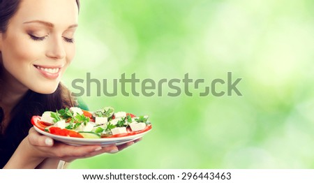 Young beautiful smiling brunette woman with plate of salad, outdoor, with blank copyspace area for slogan or text message - stock photo
