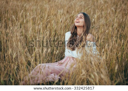 Young beautiful smiling girl wearing white  and pink dress sitting in wheat field - stock photo