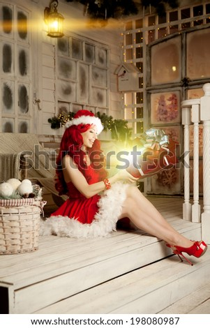 Young beautiful smiling santa woman. Christmas Fashionable luxury girl celebrating New Year holding gift in hands  - stock photo