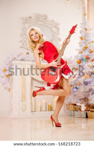 Young beautiful smiling santa woman near the Christmas tree with bunny. Fashionable luxury  girl celebrating New Year with electric guitar  - stock photo