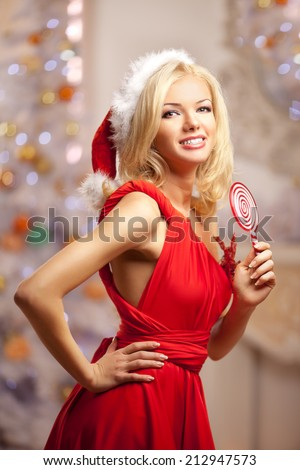 Young beautiful smiling santa woman near the Christmas tree with bunny. Fashionable luxury  girl celebrating New Year.  - stock photo
