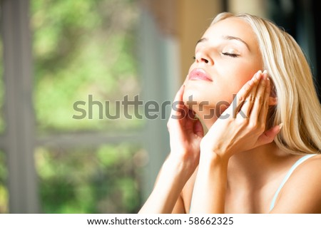 Young beautiful smiling woman applying creme - stock photo