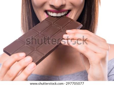 Young beautiful smiling woman eating bar of  dark chocolate. Studio shot. Close-up. - stock photo