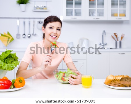 Young beautiful smiling woman eating salad in the kitchen - stock photo