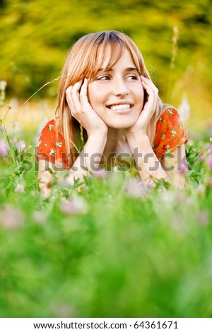 Young beautiful smiling woman in red dress lies on green summer meadow. - stock photo