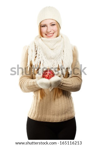 Young beautiful smiling woman in winter clothing with red christmas tree ball - stock photo