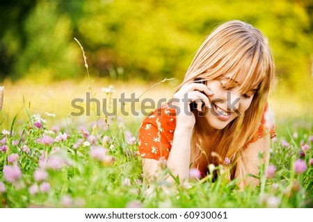 Young beautiful smiling woman lies on lawn and talks by mobile phone. - stock photo
