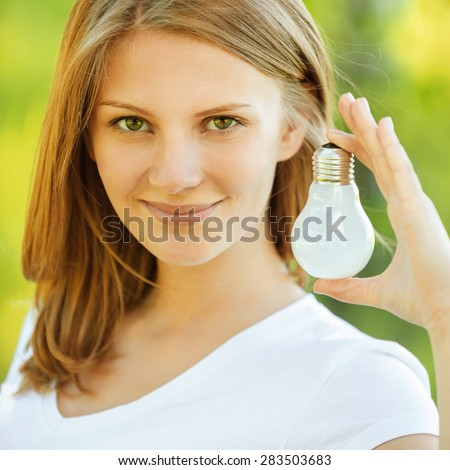 Young beautiful smiling woman shows incandescent lamp, on green background of summer city park. - stock photo