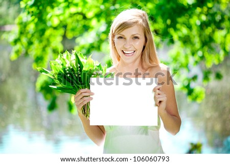 Young beautiful smiling woman with blank poster  outdoors - stock photo