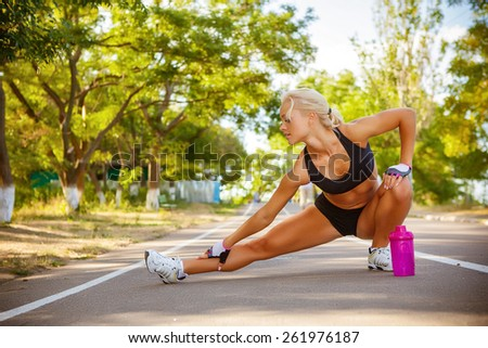 young beautiful sportswoman outdoor doing exercises - stock photo