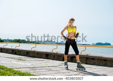 Young, beautiful, sporty and fit girl rollerblading on skates - stock photo