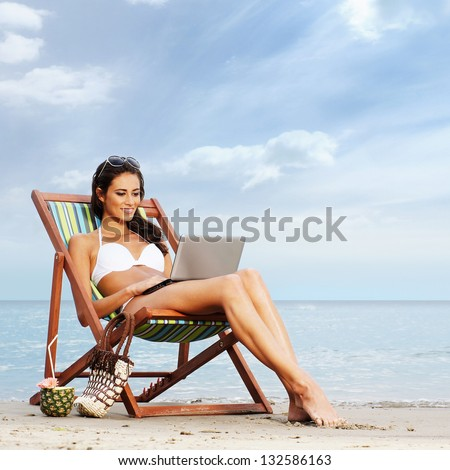 Young, beautiful, sporty and sexy woman with the notebook pc relaxing on the beach - stock photo