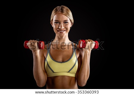 Young beautiful sporty blonde on black background. Fit sportswoman exercising with red dumbbells - stock photo