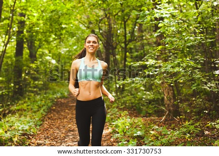 Young beautiful sporty girl in short green sports top training in green forest during summer autumn season with lots of leaves fallen. Front view with copy space  - stock photo