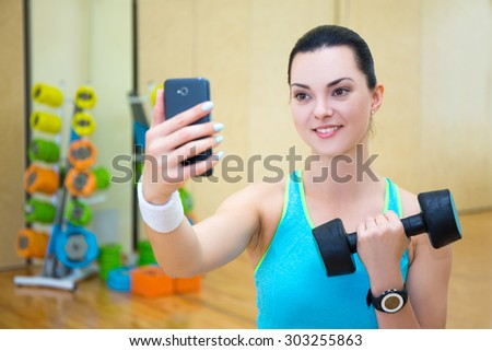 young beautiful sporty woman making selfie photo with dumbbell on smartphone in gym - stock photo