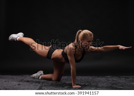 Young beautiful sporty woman on black background. Fit sportswoman stretching - stock photo