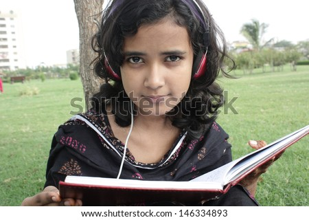 Young beautiful student reading book and listening music. - stock photo