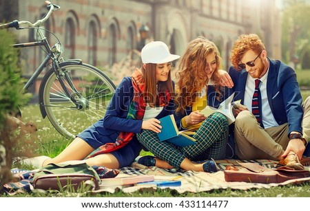 Young beautiful students are sitting and reading near university - stock photo