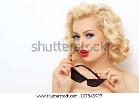 Young beautiful stylish blond woman with vintage sunglasses, over white wall - stock photo