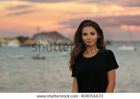 Young beautiful stylish girl wearing simple black t-shirt posing near sea at sunset - stock photo