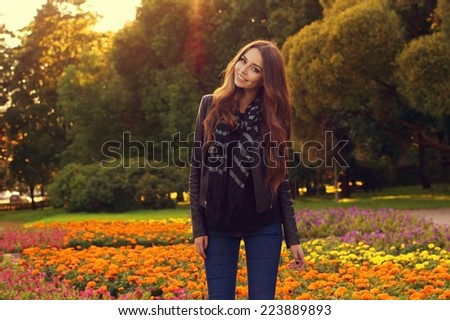young beautiful stylish woman posing against colorful flowers and trees at sunset. Fashion style autumn or fall portrait of pretty girl standing outdoors - stock photo