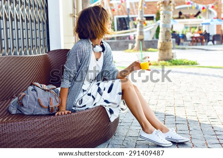 Young beautiful stylish woman, sitting on the street bench, traveling alone, enjoy her free time, wearing vintage hipster trendy outfit, drinking smoothie, enjoy weekends. - stock photo