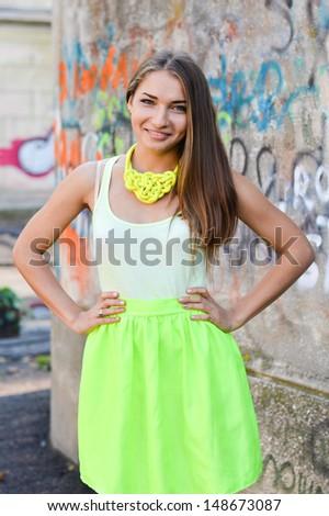 Young beautiful stylish woman standing at graffiti wall street fashion on the summer outdoors background - stock photo