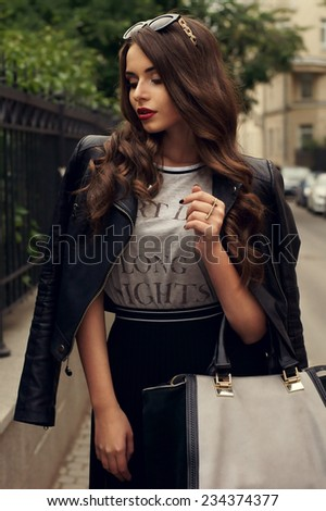 Young beautiful stylish woman with long curly hair posing at street in black skirt, gray t-shirt and leather jacket. - stock photo