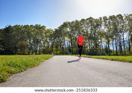 young, beautiful successful fitness woman running in the park, a beautiful sunny day - stock photo