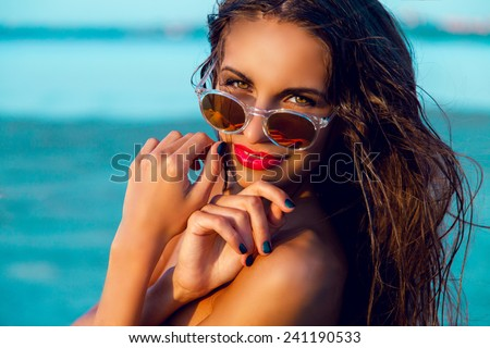 Young beautiful tanned fitness girl with beautiful big eyes and red lips posing on the  tropical evening beach . Wet hair and perfect skin .Close up portrait . - stock photo