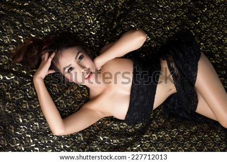 Young beautiful tanned Sexy Asian woman wearing elegant lingerie lying on bed - stock photo