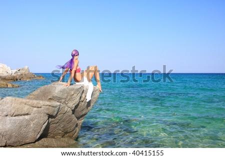 Young beautiful tanned woman in bikini meditating by the sea in Greece - stock photo