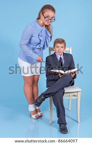 Young beautiful teacher helping schoolboy to study - stock photo