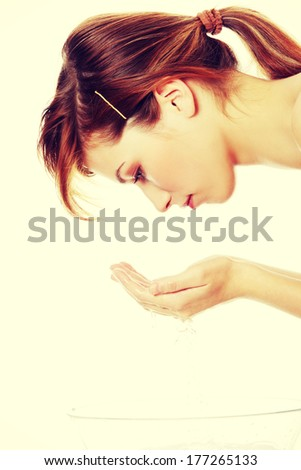 Young beautiful  teen woman washing her face, isolated on white  - stock photo