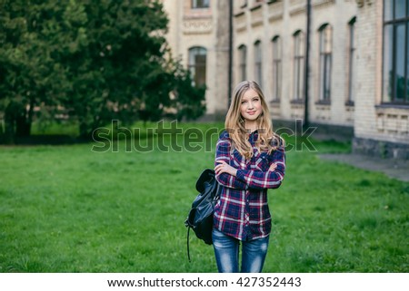 Young beautiful teenager girl student of the graduate applicant standing near the campus, university, school, education with a backpack choice, spring green park, mysterious look, smart idea - stock photo