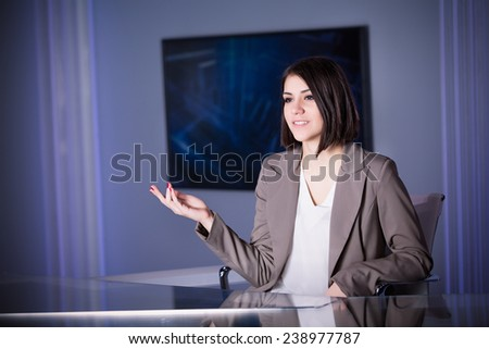 Young beautiful television announcer talking to audience at studio during live broadcasting.Transmission with serious smiling journalist woman.Television anchorwoman at studio during live broadcasting - stock photo