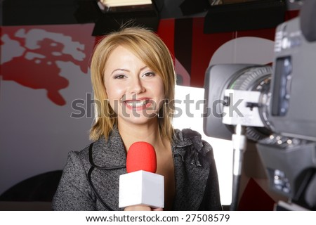 young beautiful television news reporter in front of the video camera smiling and looking at the camera in studio in live transmission - stock photo