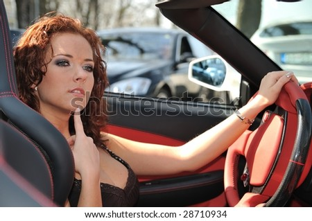Young beautiful thoughtful woman sitting in sport car - red interior detail - stock photo