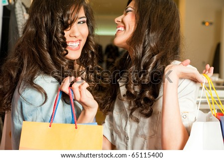 Young beautiful twin girls laughing and holding shopping bags in a store - stock photo
