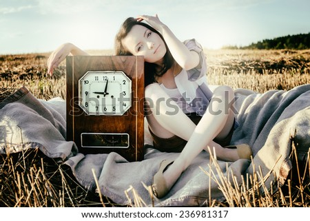 young beautiful unusual girl illustrates conceptual idea with watch - stock photo