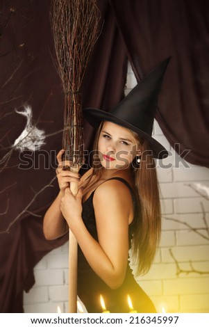 Young beautiful witch  with hat and broom - stock photo