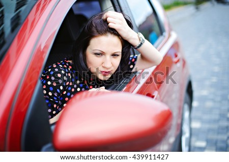 Young beautiful woman admires in a car mirror. - stock photo