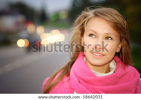 Young beautiful woman against evening city street. - stock photo