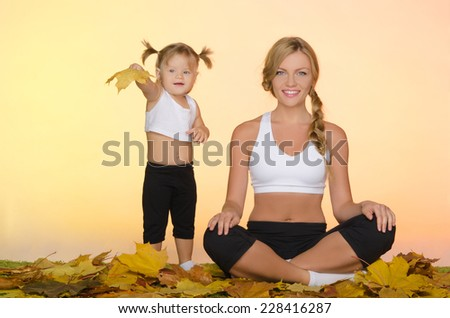 young beautiful woman and child doing yoga in fall - stock photo