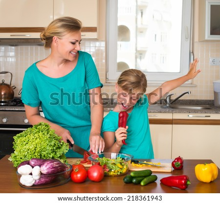 Young beautiful woman and girl making fresh vegetable salad. Healthy domestic food concept. Smiling mother and funny playful daughter cooking together, help children to parents. - stock photo