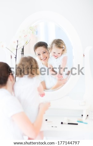 Young beautiful woman and her cute funny toddler daughter applying make up and cosmetics with a brush sitting in front of a round mirror in a white sunny bedroom  - stock photo
