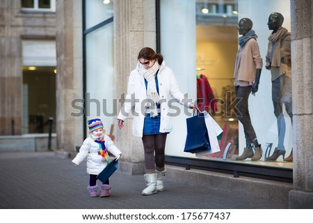 Young beautiful woman and her cute toddler daughter enjoying winter sale shopping - stock photo