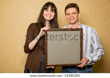 young beautiful woman and smiling man with picture in frame in hands - stock photo
