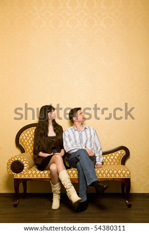 young beautiful woman and young man sitting on sofa in room, looking aside - stock photo