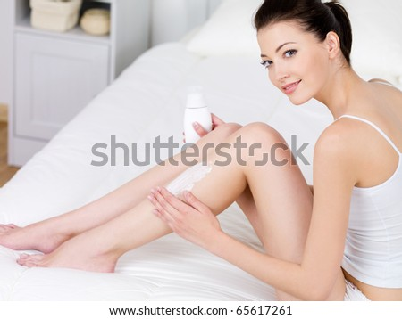 Young beautiful woman applying body lotion on her attractive legs - indoors - stock photo